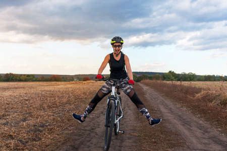enthusiastic joyful girl rides a bicycle on a field road