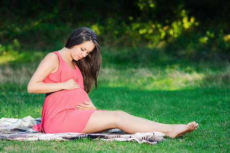 young woman sitting: Young pregnant woman relaxing in park outdoors, healthy pregnancy.