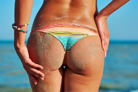 sex girl: Sexy back of a beautiful woman in color creative bikini on sea background.