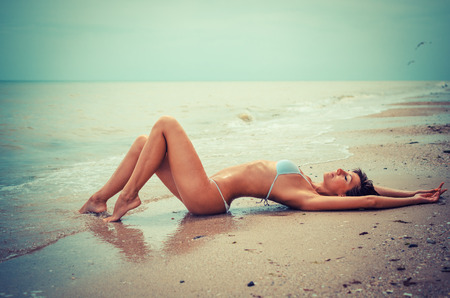Beautiful young woman laying in the sea coast - toned image