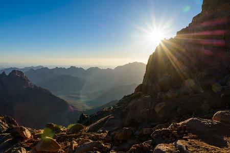 monte sinai: Egipto, Sinaí, Monte de Moisés. Vista desde la carretera en la que los peregrinos suben la montaña de Moisés y el amanecer - sol de la mañana con los rayos en el cielo. Foto de archivo