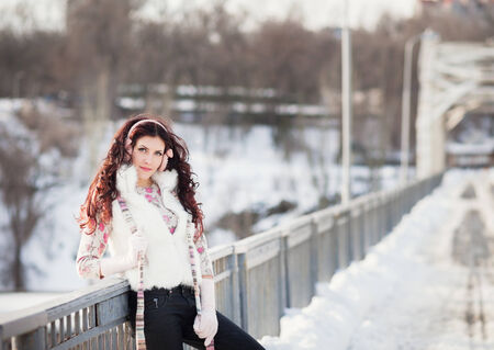 Pretty caucasian woman in a winter park with sun photo