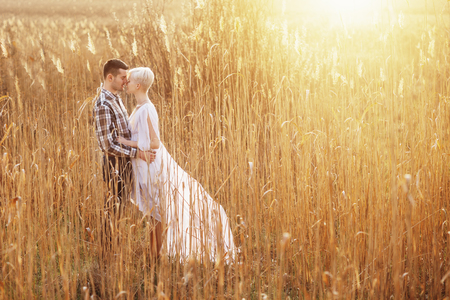 country girls: Outdoor lifestyle portrait of young couple hugging on field. Sunny warm weather. Backlight and sunset.