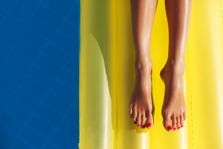 aqua naked: Portrait of beatiful tanned woman relaxing in swimming pool. Legs close up. Creative gel polish red pedicure. Hot summer day and bright sunny light.
