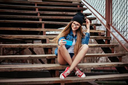 adolescente: Pareja sexy mujer inconformista rubia posando para selfie y riendo. El uso de los pantalones vaqueros de la chaqueta, inconformista sombrero negro y gafas. Retrato Estilo de vida