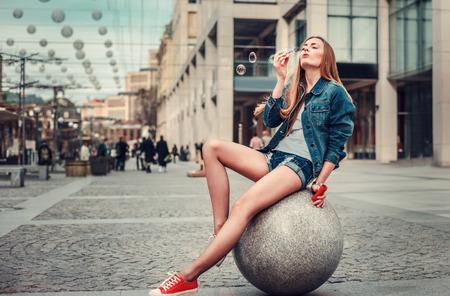 都市のかなり若い女の子吹いて気泡のアウトドア ・ ライフ スタイルの肖像画、ヒップスター盗品グランジで身に着けて都市背景をスタイルします