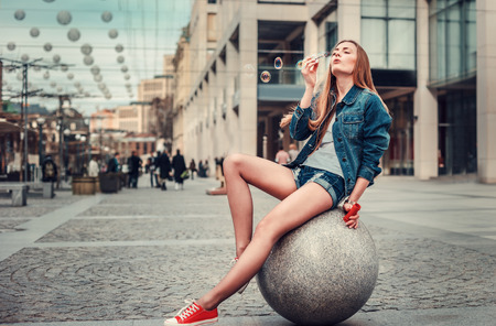 urban style: Outdoor lifestyle portrait of pretty young girl blowing bubble in the city, Wearing in hipster swag grunge style urban background. Retro vintage toned image, film simulation.