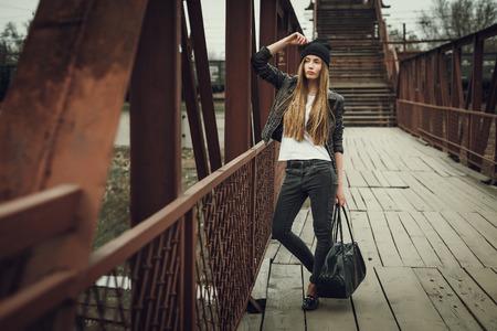 swag: Retrato al aire libre de estilo de vida de la moda de muy joven, que llevaba en el fondo urbano de estilo grunge bot�n inconformista. Imagen de la vendimia retro tonificado, simulaci�n de pel�cula. Foto de archivo