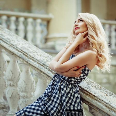 Fashion outdoor portrait of beautiful elegant blonde woman wearing pin up style, posing on the stairway Standard-Bild