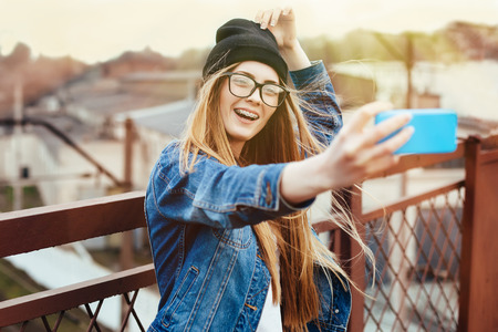 Young sexy blonde hipster woman posing for selfie and laughing. Wearing jeans jacket, hipster black hat and glasses. Lifestyle portrait bright with sun shine. Standard-Bild