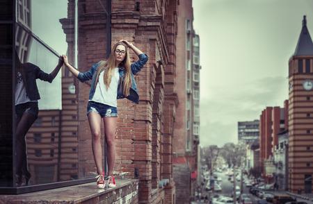 힙 스터 장식이 드레스를 입고 높은 건물 난간의 가장자리에가는 꽤 젊은 여자의 야외 라이프 스타일 초상화,,, 도시 배경입니다. 레트로 빈티지, 필름  스톡 콘텐츠