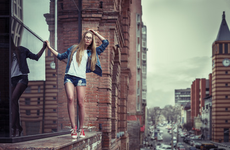 Outdoor lifestyle portrait of pretty young girl, going on the edge of high building parapet, wearing hipster swag dress, urban background. Retro vintage toned image, film simulation.