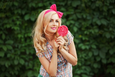 sexy pose: Fashion outdoor portrait of beautiful elegant blonde woman wearing pin up style, posing with rose lollipop. Green nature background. Retro vintage toned image, film simulation. Stock Photo