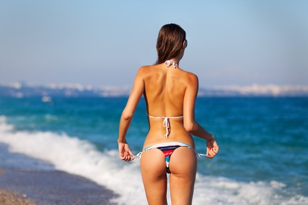 nude butt: Sexy back of a beautiful tanned woman in creative striped bikini on sea background. Sexy buttocks.