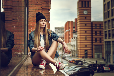 Outdoor lifestyle portrait of pretty young sitting girl, wearing in hipster swag grunge style urban background. Retro vintage toned image, film simulation. Standard-Bild