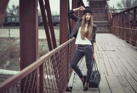 estilo urbano: Retrato al aire libre de estilo de vida de muy joven, que llevaba en el fondo urbano de estilo grunge botín inconformista. Imagen de la vendimia retro tonificado, simulación de película. Foto de archivo