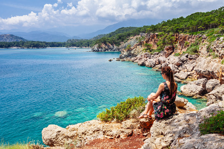sunny south: Tourist girl sitting and looking on bay of old greek town Phaselis. Panoramic view on coast near Kemer, Antalya, Turkey.