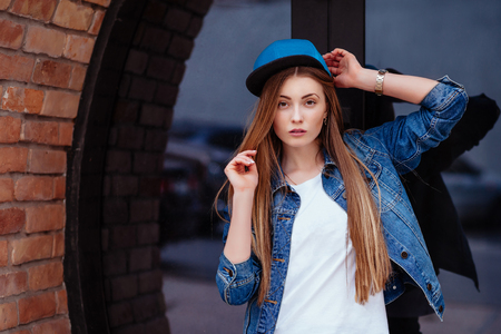 sexy glamour: Young sexy glamour woman wearing jeans jacket and baseball cap. Lifestyle city portrait in swag style. Stock Photo