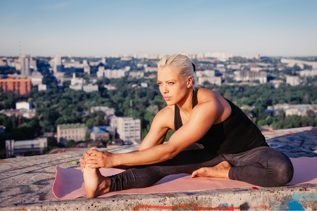muscular build: Portrait of beautiful blonde strong woman in sportwear doing workout stretching on the roof of a skyscraper above the big city at early morning. Female sporty muscular body. Dawn and sunrise bright sunny light. Stock Photo