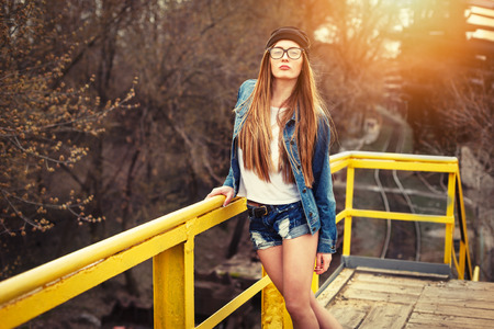 Outdoor lifestyle portrait of pretty young girl, wearing bright hipster swag dress, urban background.