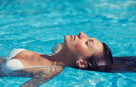 aqua naked: Portrait of beautiful tanned woman in white swimwear relaxing in swimming pool spa. Hot summer day and bright sunny light. Stock Photo