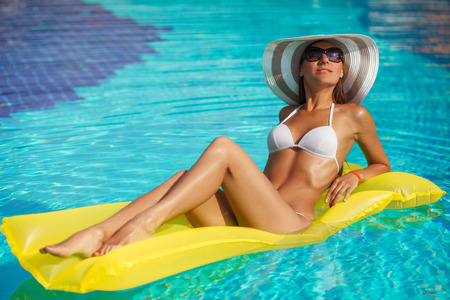 aqua naked: Portrait of beautiful tanned woman relaxing in swimming pool in white swimwear, hat and sunglasses. Creative gel polish manicure and pedicure. Hot summer day and bright sunny light.