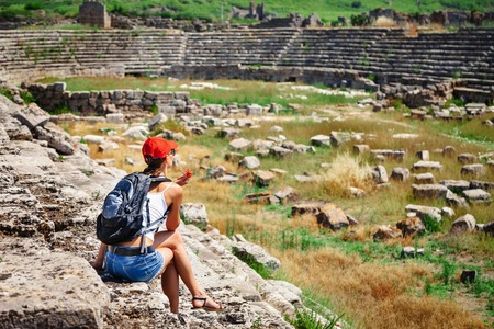 antik: Pretty tourist woman with backpack at the ruins of ancient city of Perge near Antalya Turkey Stock Photo
