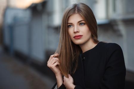 Schöne blonde junge Frau in schönen schwarzen Mantel. Aufstellung auf städtischen Hintergrund. Fashion Foto