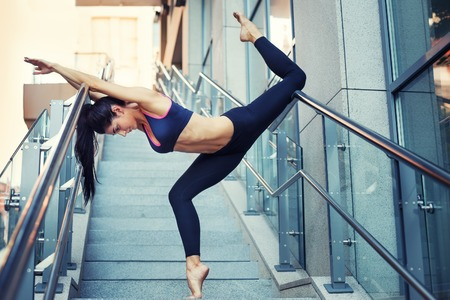 Portrait of beautiful strong woman in sportwear doing workout yoga exercise and stretching on the stairway. Female sporty muscular body.
