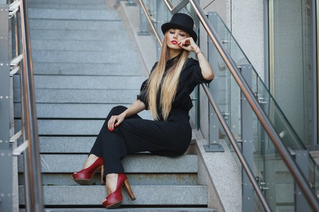vogue style: Beautiful young fashionable woman posing in black suite, red shoes with high heels and black hat. Vogue style. Urban background