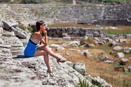 antik: Pretty tourist woman with red flower in creative dress ans high heels at the ruins of ancient city of Perge near Antalya Turkey Stock Photo