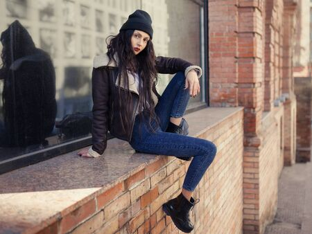 Outdoor lifestyle fashion portrait of pretty young girl, wearing in hipster swag grunge style on urban background. Wearing hat and jeans. Spring fashion woman. Toned style instagram filters.