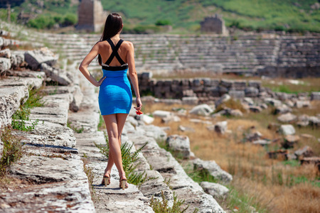 Pretty tourist woman with red flower in creative dress ans high heels at the ruins of ancient city of Perge near Antalya Turkey Stock Photo