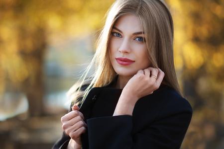 Bella bionda giovane donna in bel cappotto nero. In posa su sfondo dorato autunno. Foto di moda Archivio Fotografico