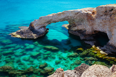 greco: Beautiful natural rock arch near of Ayia Napa, Cavo Greco and Protaras on Cyprus island, Mediterranean Sea. Legendary bridge lovers. Amazing blue green sea and sunny day. Stock Photo