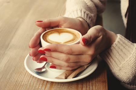 Close-up female hands holding cup with coffee cappuccino with foam with pattern heart. Perfect red gel polish manicure. Wood natural table. Creative color warm post processing  style.