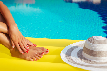 aqua naked: Portrait of beautiful tanned woman relaxing in swimming pool. Legs and hands close up. Creative gel polish red pedicure and manicure. Hot summer day and bright sunny light.