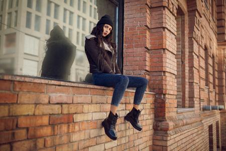 retrato vida al aire libre de muy joven, vestido con estilo grunge botín inconformista en el fondo urbano. Que lleva el sombrero y pantalones vaqueros con mochila. mujer de moda de primavera.
