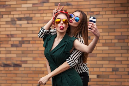 Two young sexy fashion women posing for selfie and laughing with tonque. Lifestyle portrait on street city background Stock fotó
