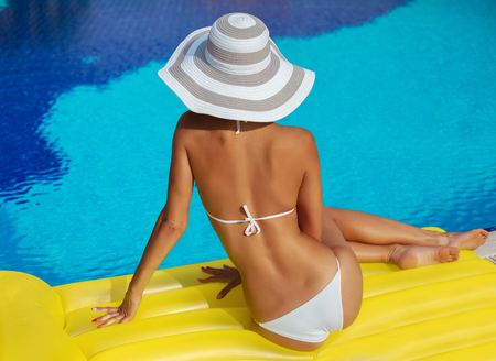 naked woman back: Portrait of beautiful tanned woman relaxing in swimming pool in white swimwear, hat and sunglasses. Creative gel polish manicure and pedicure. Hot summer day and bright sunny light.