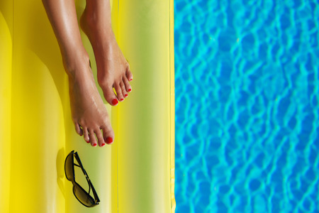 aqua naked: Portrait of beautiful tanned woman relaxing in swimming pool. Sunglasses and inflatable mattress. Legs close up. Creative gel polish red pedicure and manicure. Hot summer day, bright sunny light.