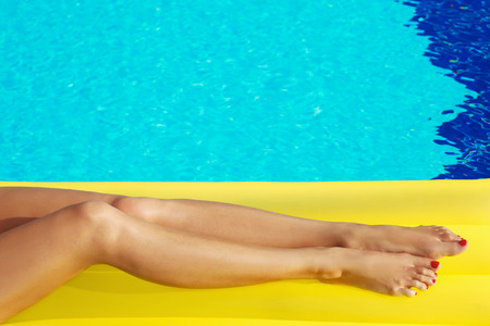 aqua naked: Portrait of beautiful tanned woman relaxing in swimming pool. Yellow inflatable matress. Legs close up. Creative gel polish red pedicure and manicure. Hot summer day, bright sunny light.