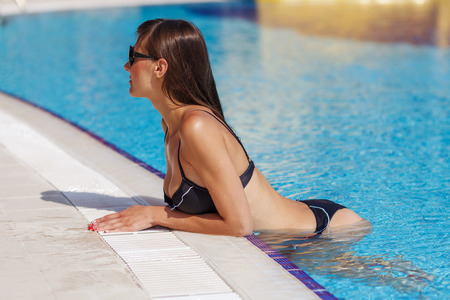 aqua naked: Portrait of beautiful tanned woman relaxing in swimming pool in black swimwear. Creative gel polish manicure and pedicure. Hot summer day and bright sunny light.