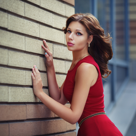 Outdoor lifestyle portrait of pretty young girl posing on stairway, wearing in red dress on urban background.