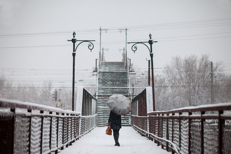 Young woman is going across the bridge in snowfall