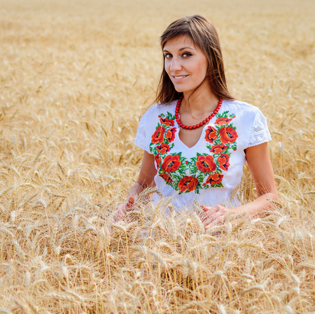 Beauty girl outdoors on the wheat field, woman dressed in national dress. Blowing long hair. 스톡 콘텐츠