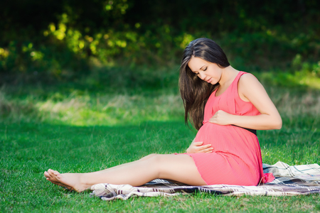 Young pregnant woman relaxing in park outdoors, healthy pregnancy