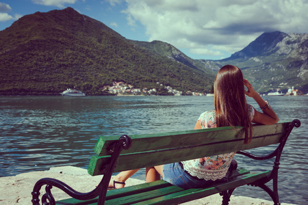 Beautiful young woman looking and waiting at the seacoast. Sunny day. Montenegro, Europe. Retro style toning image.