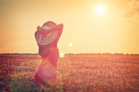 Beautiful young woman with brown hear wearing rose dress and hat with raised arms enjoying outdoors looking to the sun on perfect wheat field on sunset