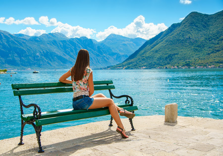 Beautiful young woman looking at the sea. Montenegro, Europe. Toning image.